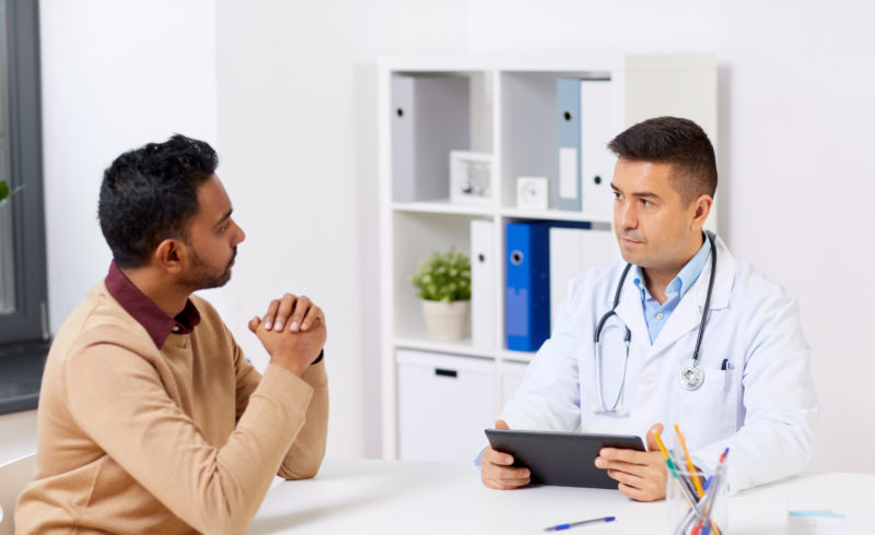indian patient looking matter of factly at doctor giving results