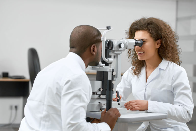 optician looking through tool at patient's eyes