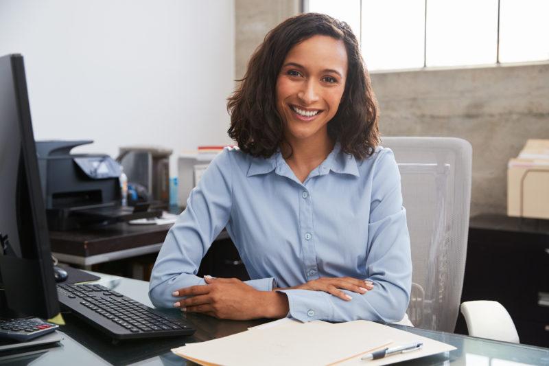 women sitting at desk smiling