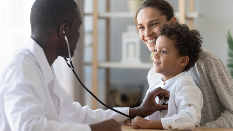 african american doctor checking african american baby's heart