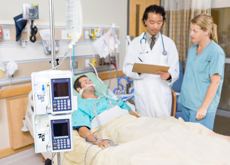 doctors looking together at results over patient in hospital bed