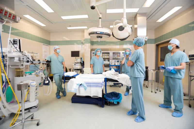 surgeons standing around operating room