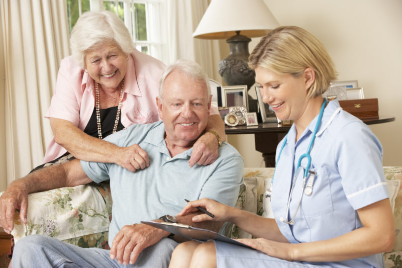 retired elderly man at home having visit with doctor