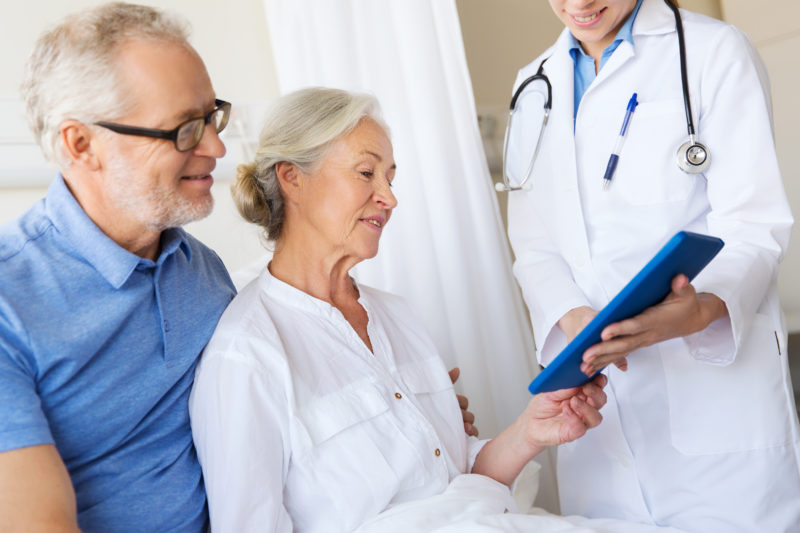 older couple looking at doctor results in office